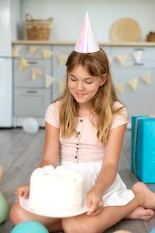 Pełna strzał urodzinowa dziewczyna trzyma tort