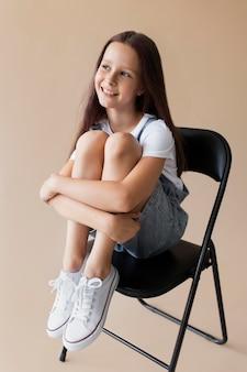 Pełna strzał uśmiechnięta dziewczyna siedzi na krześle