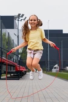 Pełna strzał uśmiechnięta dziewczyna skacząca czerwona lina