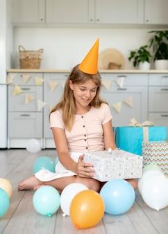 Pełna strzał uśmiechnięta dziewczyna trzyma prezent