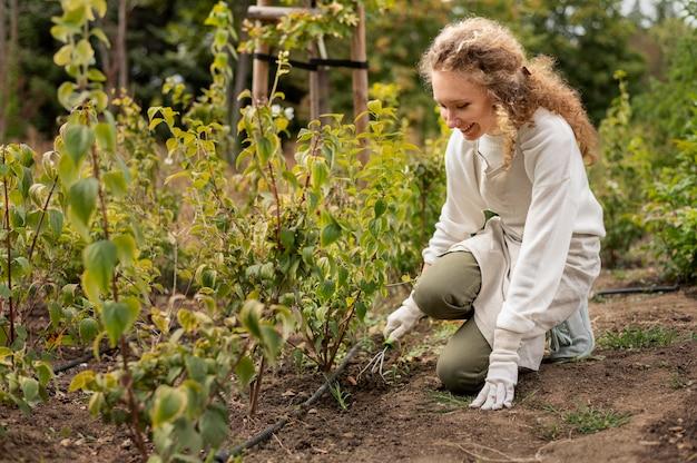 Pełna strzał uśmiechnięta kobieta ogrodnictwo