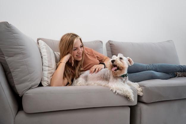 Pełna strzał uśmiechnięta kobieta pieszczący psa