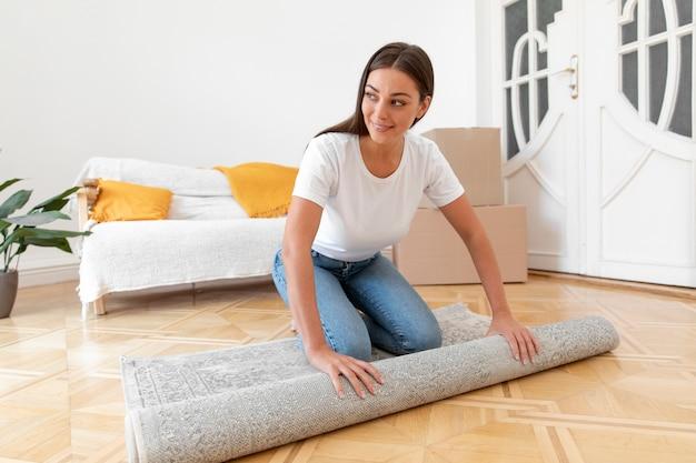 Pełna strzał uśmiechnięta kobieta rozkładająca dywan