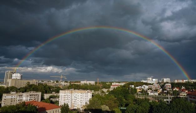 Pełna tęcza nad lwowem na ukrainie z zachmurzonym ciemnym niebem