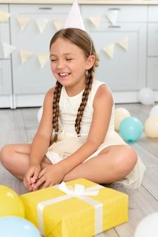 Pełna uśmiechnięta dziewczyna na podłodze
