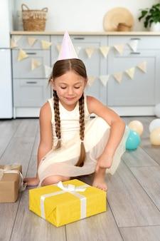 Pełna uśmiechnięta dziewczyna z prezentem