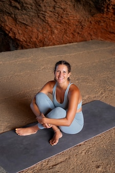 Pełna uśmiechnięta kobieta na macie do jogi