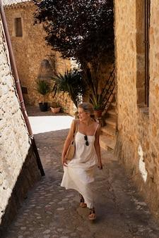 Pełna uśmiechnięta kobieta odwiedzająca stare miasto