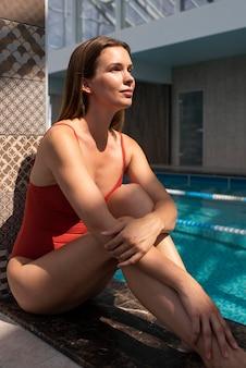 Pełna uśmiechnięta kobieta relaksująca się w pobliżu basenu