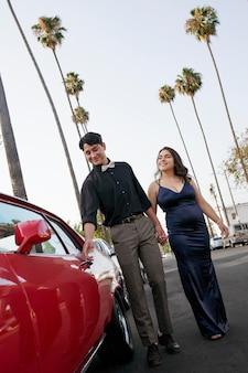 Pełna uśmiechnięta para z samochodem