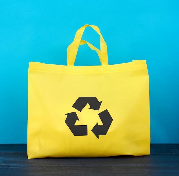 Pełna wielokrotnego użytku żółta wiskozowa torba na błękitnym drewnianym tle