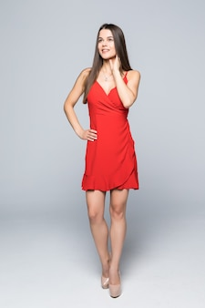 Pełna wysokość atrakcyjnej kobiety mody w wąskiej czerwonej sukience chodzącej po ścianie.