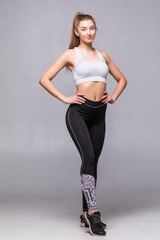 Pełne ciało młodej wesoły uśmiechnięta kobieta w odzieży sportowej, na białym tle