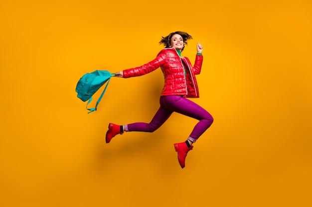 Pełne ciało profilowe zdjęcie z boku wesoła dziewczyna skacząca wykłady w szkole średniej trzymaj niebieską torbę nosić fioletowe spodnie stylowe modne spodnie czerwone buty