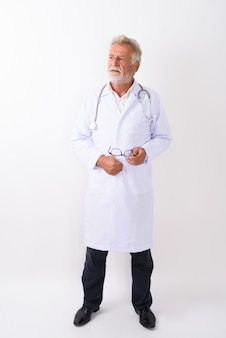 Pełne ciało strzał przystojny starszy brodaty mężczyzna lekarz stojąc i myśląc trzymając okulary na białym tle
