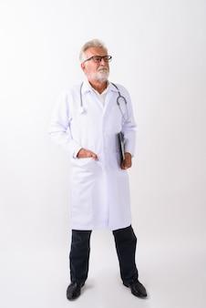 Pełne ciało strzał przystojny starszy brodaty mężczyzna lekarz stojąc i myśląc trzymając schowek na białym tle