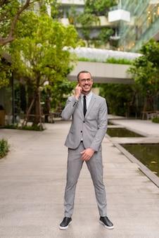 Pełne ciało strzał szczęśliwy łysy biznesmen brodaty hiszpanie noszenie okularów z naturą w mieście