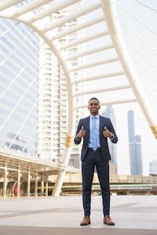 Pełne ciało strzał szczęśliwy młody biznesmen daje kciuki do góry w mieście na zewnątrz