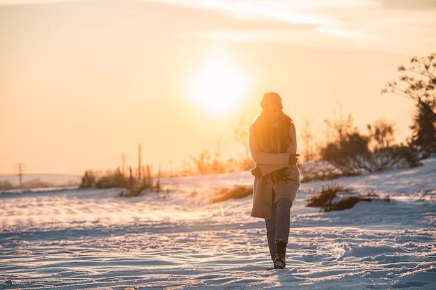 Pełne ciało szczęśliwa młoda kobieta w ciepłych ubraniach spacerując po świeżym białym śniegu w zimowej wsi w czasie zachodu słońca