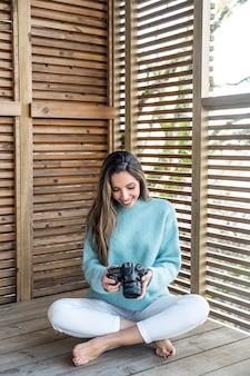 Pełne ciało wesołej młodej kobiety boso w ubranie z aparatem fotograficznym w rękach siedzącej na drewnianym tarasie