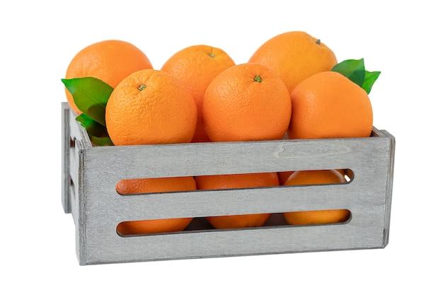 Pełne drewniane pudełko pomarańczy na białym tle