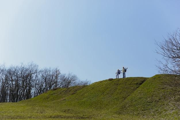 Pełne i swobodne oddychanie. starsza rodzina para mężczyzna i kobieta w strój turystyczny spaceru na zielonym trawniku w pobliżu drzew w słoneczny dzień. pojęcie turystyki, zdrowego stylu życia, relaksu i wspólnoty.