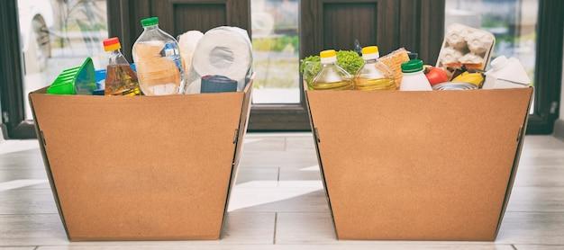 Pełne kartonowe pudełko ekologiczne z produktami ze sklepu spożywczego na podłodze w domu przy drzwiach