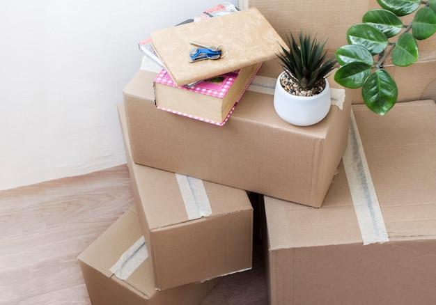 Pełne pudełka rzeczy z kwiatami w pomieszczeniach i kluczami do nowego domu przenoszącego się do innego widoku z góry