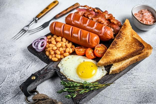 Pełne smażone angielskie śniadanie składające się z jajek sadzonych, kiełbasek, bekonu, fasoli i tostów na drewnianej desce do krojenia. białe tło. widok z góry.