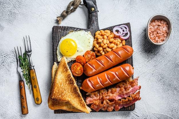 Pełne smażone angielskie śniadanie składające się z jajek sadzonych, kiełbasek, bekonu, fasoli i tostów na drewnianej desce do krojenia