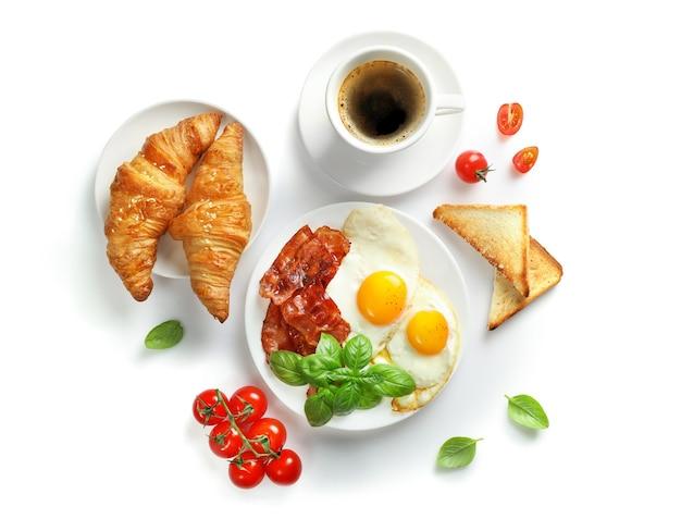 Pełne śniadanie amerykańskie ze smażonymi jajkami i pieczonym boczkiem na białym tle.