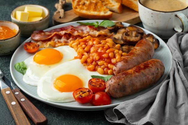 Pełne śniadanie angielskie na talerzu ze smażonymi jajkami