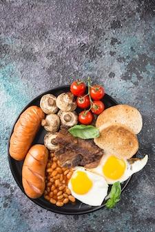 Pełne śniadanie angielskie z jajkiem sadzonym, kiełbasą, bekonem, fasolą, grzankami i pomidorami na ciemnym kamieniu