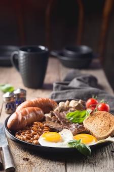 Pełne śniadanie angielskie z jajkiem sadzonym, kiełbasą, bekonem, fasolą, grzankami i pomidorami na rustykalnym drewnie