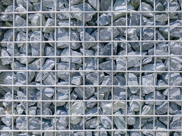 Pełne tło ramy ściany z kamieni żwirowych z metalową siatką drucianą