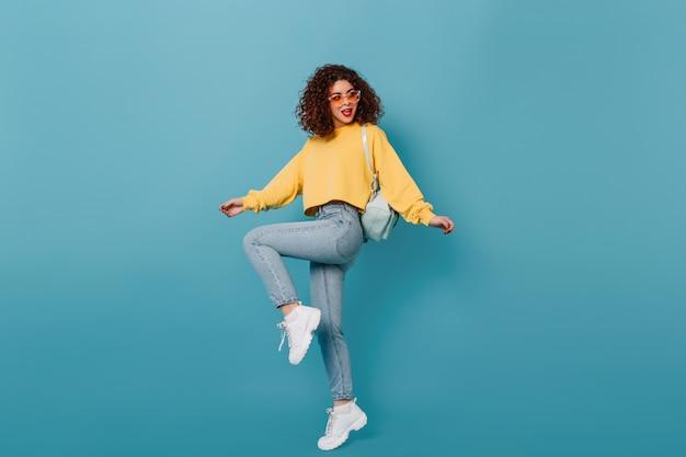 Pełne ujęcie aktywnej dziewczyny w obcisłych dżinsach i żółtej bluzie unoszącej nogę na niebieskiej przestrzeni.