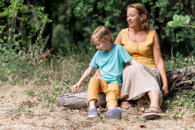 Pełne ujęcie babci i dziecka siedzącego na zewnątrz
