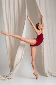 Pełne ujęcie baletnicy stojącej na pointe buta