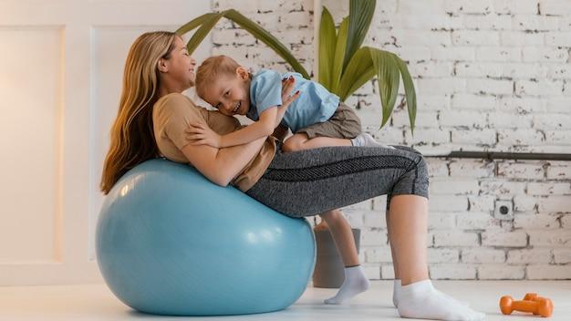 Pełne ujęcie buźki kobieta i dziecko na piłce gimnastycznej