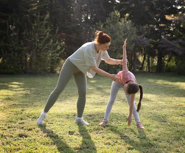 Pełne ujęcie ćwiczeń kobiety i dziecka na zewnątrz
