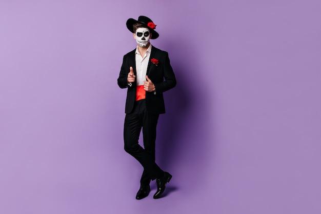 Pełne ujęcie czarującego faceta z czerwonym satynowym paskiem pod czarną marynarką, pozującego w kostiumie na halloween.