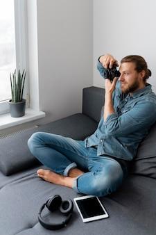 Pełne ujęcie człowieka robiącego zdjęcia w pomieszczeniach