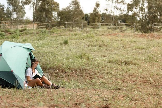 Pełne ujęcie czytającej kobiety w pobliżu namiotu
