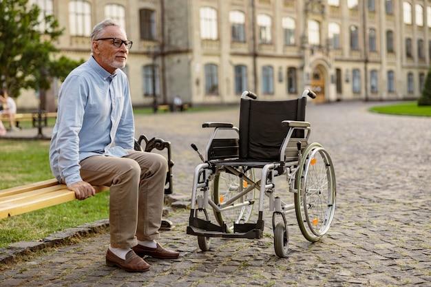 Pełne ujęcie dojrzałego pacjenta na wózku inwalidzkim, siedzącego na ławce w pobliskim parku