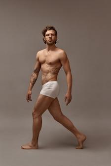 Pełne ujęcie dopasowanego atrakcyjnego wytatuowanego mężczyzny z muskularnym idealnym ciałem chodzącym na białym tle w białych bokserkach. przystojny brodaty facet demonstrujący swoje mięśnie, mający pewny siebie wygląd