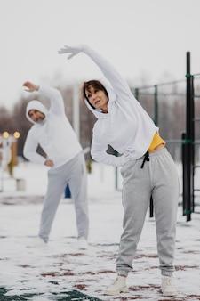 Pełne ujęcie dorosłych ćwiczących na świeżym powietrzu