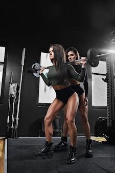 Pełne ujęcie dwóch młodych kobiet w odzieży sportowej, stojących razem na siłowni. siostra w klubie fitness patrząc na kamery.
