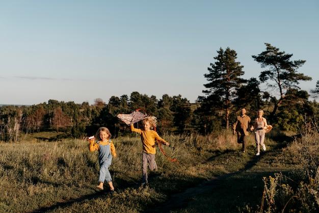 Pełne ujęcie dzieci bawiące się latawcem na łonie natury