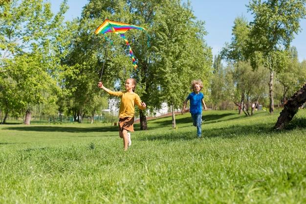 Pełne ujęcie dzieci biegających z latawcem