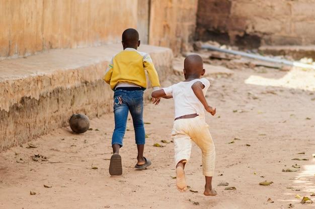 Pełne ujęcie dzieci biegnące po piłce